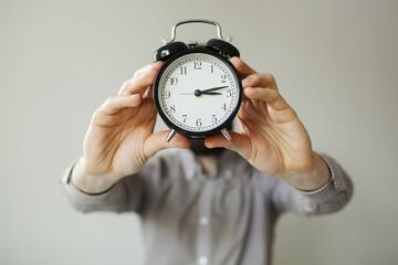 Man with alarm clock head in hands
