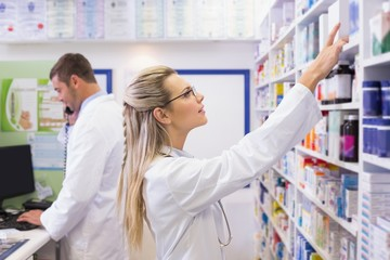 Pharmacist looking up at medicines