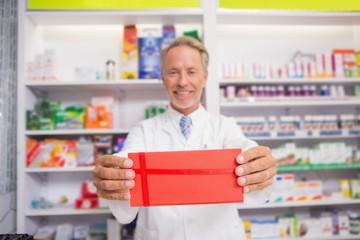 Smiling senior pharmacist presenting paper