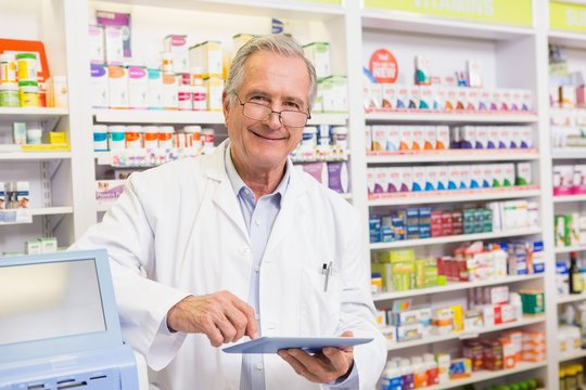 Smiling pharmacist using tablet pc