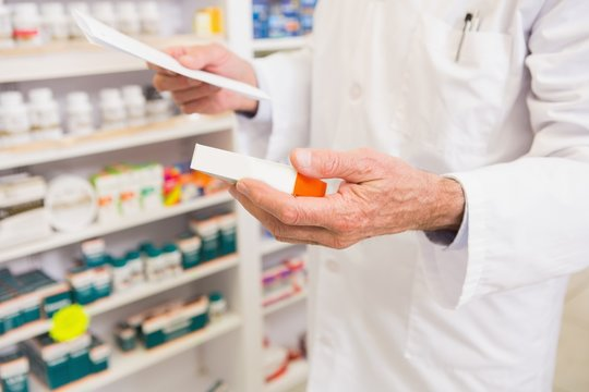Pharmacist looking at prescription and medicine