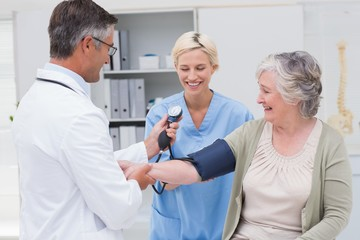 Doctor and nurse checking senior patients blood pressure