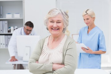 Patient smiling while doctor and nurse working in background