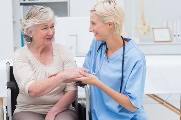 Female nurse checking flexibility of patients wrist