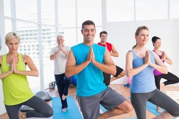People practicing tree pose in fitness studio