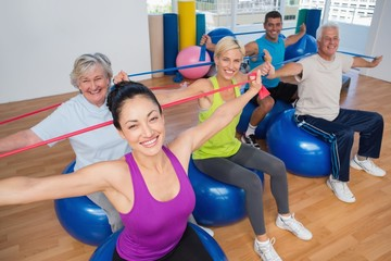 People exercising with resistance bands in gym