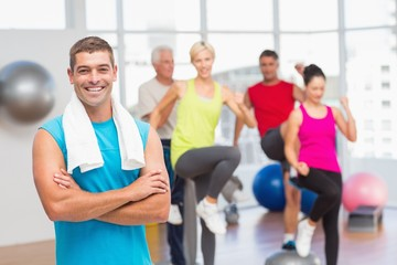 Fit man standing arms crossed at gym