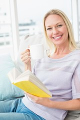 Happy woman having coffee while reading book on sofa
