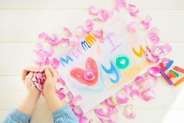 Girl Holding Rose Petals with Drawing for Mummy on the backgroun