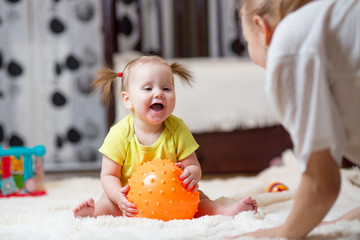 mom playing ball with baby indoor