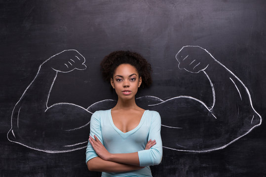 Serious afro-american woman with painted muscular arms on