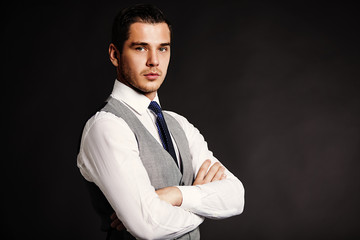 Handsome young business man standing on black background