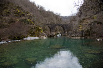 Beautiful turquoise pond and old stone bridge