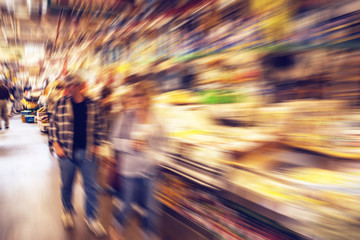 People shopping groceries in a public market - radial blur