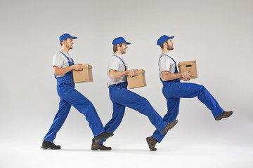 Three guys walking with boxes
