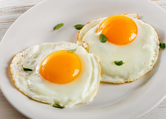Two fried eggs on white plate for healthy breakfast