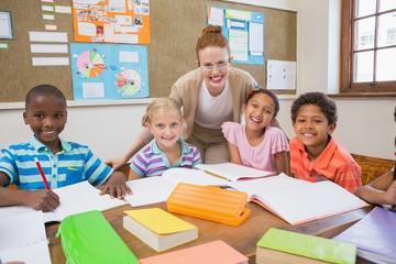 Pretty teacher helping pupils in classroom