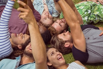 Happy young friends lying on grass
