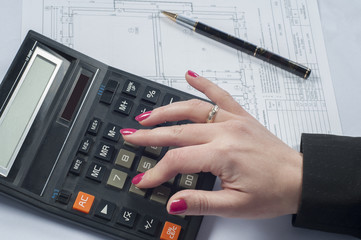Business woman counting with a calculator