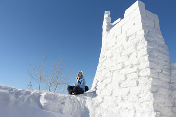 The woman sitting at snow fortress