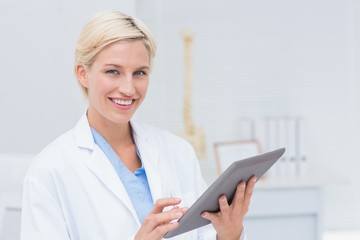 Confident female doctor using digital tablet