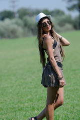 Woman on grass with hat and sunglasses on bright sunny day
