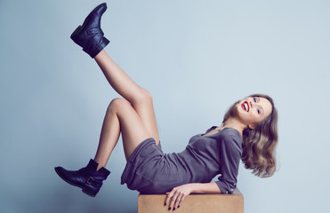 Smiling young womanl in trendy boots and dress posing in studio. Wall mural