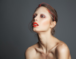 Art make up of beautiful woman. Orange lips and lashes. Body art