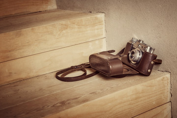 Vintage camera on wooden stairs. Instagram style toned photo