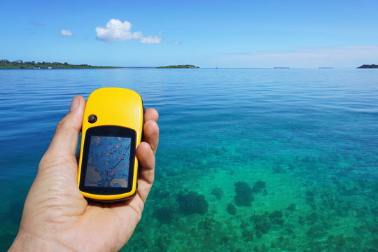 GPS satellite navigator in hand above clear water