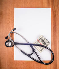 Stethoscope blank sheet of paper,  and money on a wooden table.