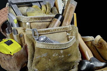 Closeup of rugged worn leather carpenters work bags with constru