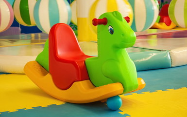Bright toy rocking horse on the playground