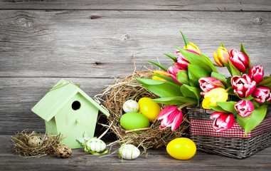 easter decoration with eggs, birdhouse and tulips. wooden backgr