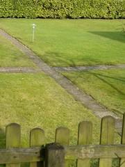 Blick über den Zaun in einen Garten mit grünem Rasen