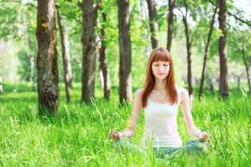 Beautiful young woman doing yoga exercises in the summer forest