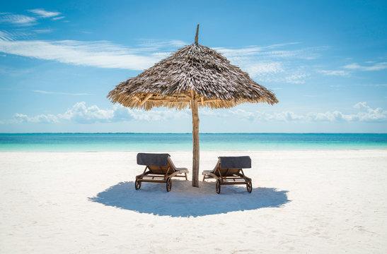 2 wooden sun loungers under a thatched umbrella on a Zanzibar tr