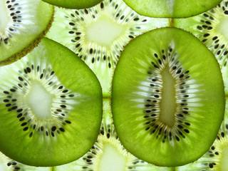 many fresh kiwi slices lit from below