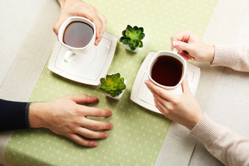 Female and male hands with cups of tea, close-up