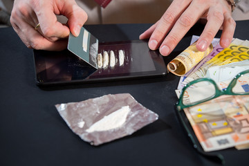 Young man preparing cocaine for sniffing using a credit card.