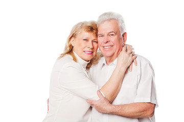 Happy mature couple embracing smiling at camera on white