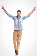 Young fashion man walking while showing the victory sign.