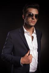 Elegant young business man arranging his jacket