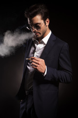 Handsome young business man blowing smoke.