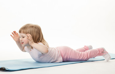 Pretty baby girl exercising lying on a training mat