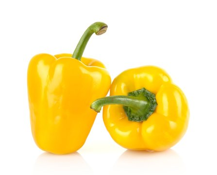 Studio shot of two yellow bell peppers isolated on white