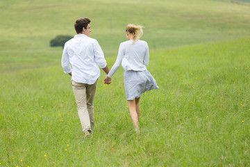 rear view of couple running outdoors