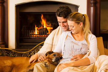 young couple sitting by fireplace with their pet dog
