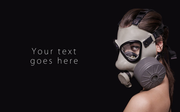 Beautiful girl wearing gas mask and looking card