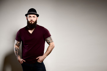 Portrait of standing handsome bearded man in hat